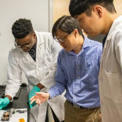 Dr. Jung working with students and colleagues in his lab.