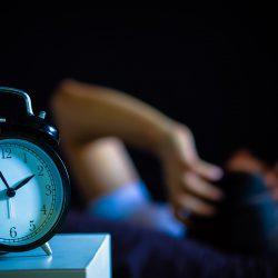 alarm clock person in bed